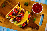 Tacos on cutting board on wooden table - 232334997