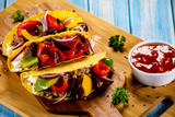 Tacos on cutting board on wooden table - 232335112