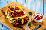 Tacos on cutting board on wooden table - 232335184