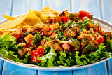 Grilled chicken meat with nachos and vegetables on wooden background - 232335588