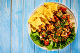 Grilled chicken meat with nachos and vegetables on wooden background - 232335958