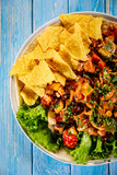 Grilled chicken meat with nachos and vegetables on wooden background - 232336164