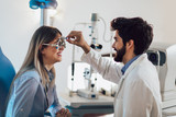 Optometrist checking patient eyesight and vision correction - 232345386