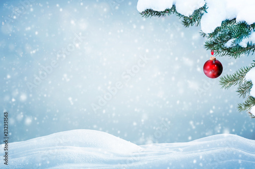 Christmas background with red ornament and falling snow on pine tree branches  - 232351563