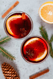 Top view on two glassses with winter Christmas traditional mulled wine with orange slices, anise and cinnamon sticks among winter decorations. - 232354343