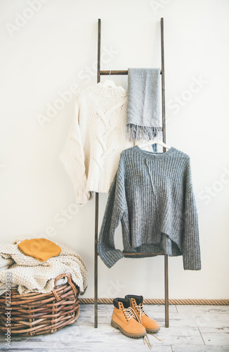 Fall or winter warm knitwear on hanger, white wall background. Fashionable female winter clothing. Woolen sweaters, grey scarf, boots and knitted hat