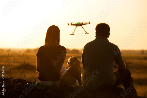 Foto Murales Happy family watching a flying drone.