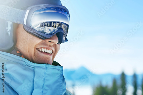 obraz lub plakat Close up of the ski goggles of a man with the reflection of snowed mountains. A mountain range reflected in the ski mask. Portrait of man at the ski resort on the background of mountains and sky