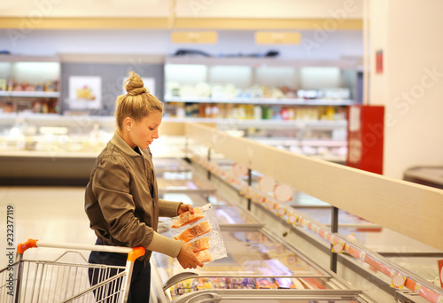Leinwandbild Motiv Woman choosing frozen food from a supermarket freezer