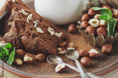 Poster Piece of chocolate cake, mint leaves, hazelnuts and jar with milk