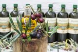 Una aceitera y aceitunas negras con hojas, botellas de aceite de oliva desenfocadas
