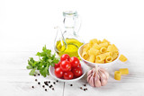 Pasta and ingredients: mezzi rigatoni, tomatoes, garlic, parsley, and extra virgin olive oil and peppercorns, on white wood background