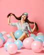 Cute caucasian sexy woman in sleep mask having fun with colorful balloon over pink background