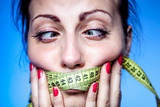 Beautiful young woman with a taped tape on the lips is worried about the diet. Selective focus on a tape. - 232388303