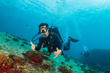 SCUBA divers swimming over a colorful tropical coral reef (Similan Islands) - 232411197