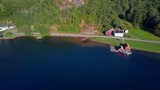 Pan footage of a small village next to a fjord. Small norwegian village. Red houses on the shore of a fjord. - 232414147