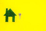 Eco friendly technologies for home concept. House silhouette made of green grass on yellow background top view copy space - 232414734
