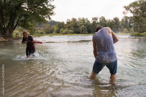 Leinwanddruck Bild young men having fun with water guns