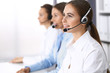 Call center. Group of operators at work. Focus on beautiful business woman in headset