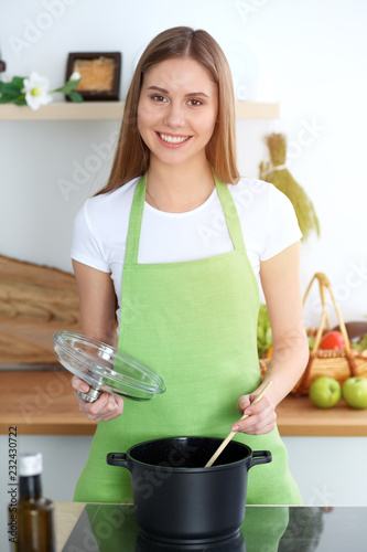 Wall mural Young happy woman cooking soup in the kitchen. Healthy meal, lifestyle and culinary concept. Smiling student girl preparing vegetarian meal at home