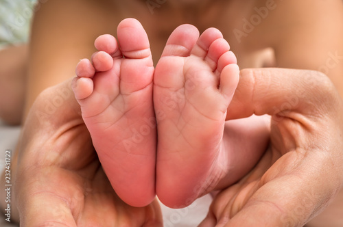 Leinwanddruck Bild Newborn baby feet in hands of mother