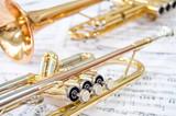 Still life. Two golden trumpets lie on notes. Brass duet.
