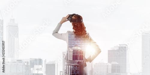 Leinwandbild Motiv Woman in mask against sunrise above city trying virtual reality