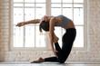 Leinwanddruck Bild - Young sporty yogi woman practicing yoga, doing Ustrasana exercise, Camel pose, working out, wearing sportswear, black pants and top, indoor full length, white yoga studio