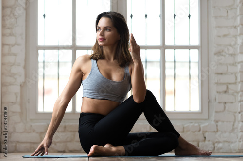 Young sporty attractive woman practicing yoga, doing Half lord of the fishes exercise, Ardha Matsyendrasana pose, working out, wearing sportswear, pants and top, indoor full length, white yoga studio