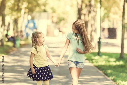 dwie małe siostry chodzą w parku