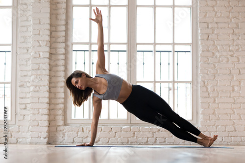 Young sporty attractive woman practicing yoga, doing Vasisthasana exercise, Side Plank pose, working out, wearing sportswear, indoor full length, yoga studio