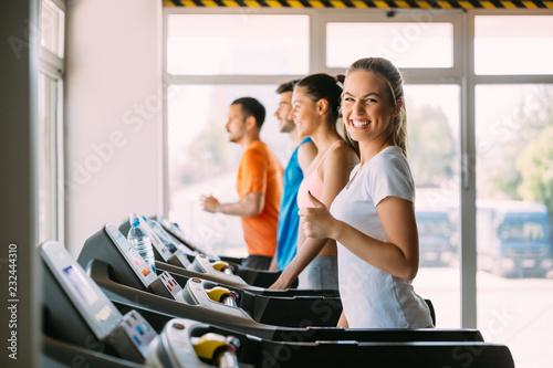 Leinwanddruck Bild Healthy man and woman running on a treadmill in a gym