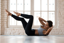 """Постер, картина, фотообои """"Young sporty woman practicing, doing crisscross exercise, bicycle crunches pose, working out, wearing sportswear, black pants and top, indoor full length, white sport studio"""""""