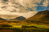 Farmhouse at the foot of the mountains in the meadow. Iceland.  - 232446780