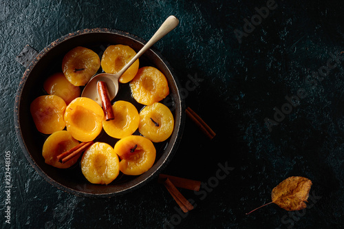 Poster Peach dessert with cinnamon and cloves on a dark background.