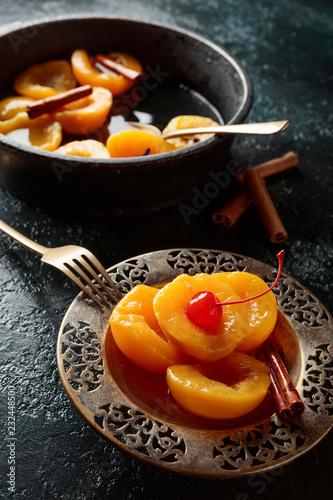 Foto Murales Peach dessert with cinnamon and  cherry on a dark background.