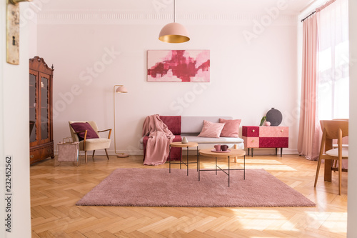 Leinwandbild Motiv Trendy living room interior with grey couch with pastel pink pillows and blanket, stylish beige armchair with burgundy pillow and retro cabinet in the corner