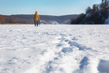 Man walking through the snow in a winter sunny day. View from the back. - 232452943