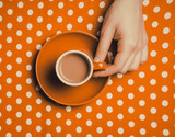 female hand holding an orange cup of coffee with milk on polka dot background. Above view - 232455930