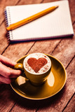 cup of coffee with cream heart shape symbol near notebook and pen on wooden table. Above view - 232456132