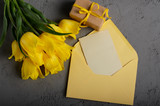 Yellow tulip near blank greeting card and envelope on grey background with space for text - 232458334