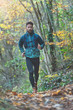 Young athlete with beard runs in the rain on a trail with technical clothing