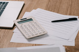 close up view of workplace with calculator, laptop, pan and notebook - 232469927