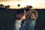 Close-up of a mother hugging her little daughter at sunset - 232472337