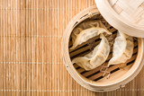 Dumplings or gyoza served in traditional steamer on bamboo mat - 232474941