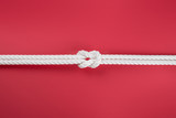 White ship ropes connected by reef knot on red - 232480748