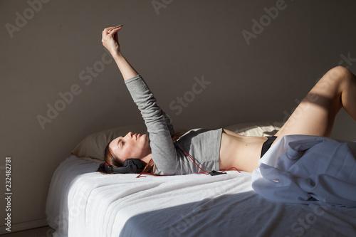 Leinwandbild Motiv beautiful woman in lingerie shoots selfie Smartphone