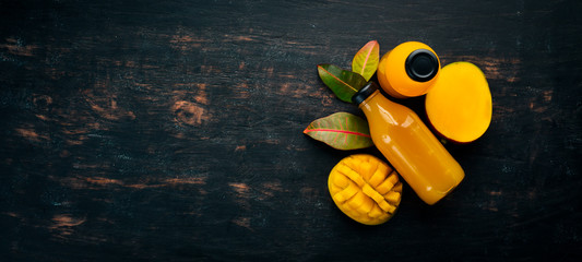 Mango and fresh juice on a black wooden background. Tropical Fruits. Top view. free space for your text. © Yaruniv-Studio