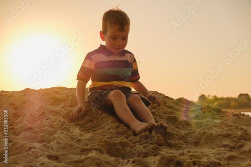 opalony pięcioletni chłopiec grający w piasku na plaży, lato