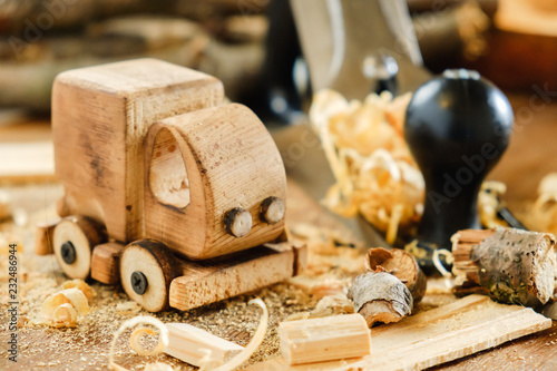 fototapeta na ścianę Wooden toy truck van car on the carpentry workbench. Hobby diy crafts, making